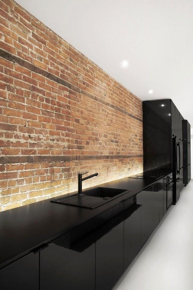Черная глянцевая кухня и фартук из кирпича смотрится дорого и стильно