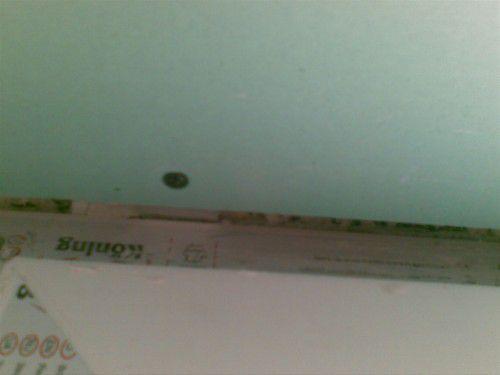 Прикладываем лист, вставляя заранее присверленные металлические полоски между рамой окна и стеной