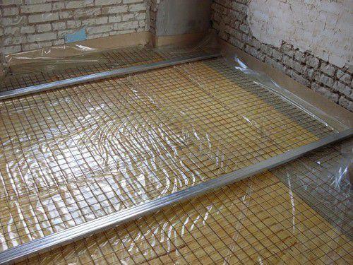 Поверх утеплителя уложена армирующая сетка и установлены маяки для заливки стяжки