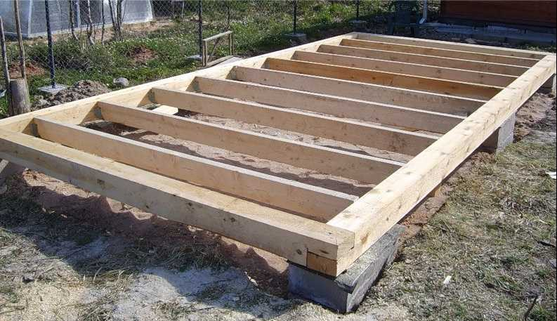 Начало строительства сарая. На фундамент уложена гидроизоляция, на нее - обвязка,, а к обвязке прикреплен брус
