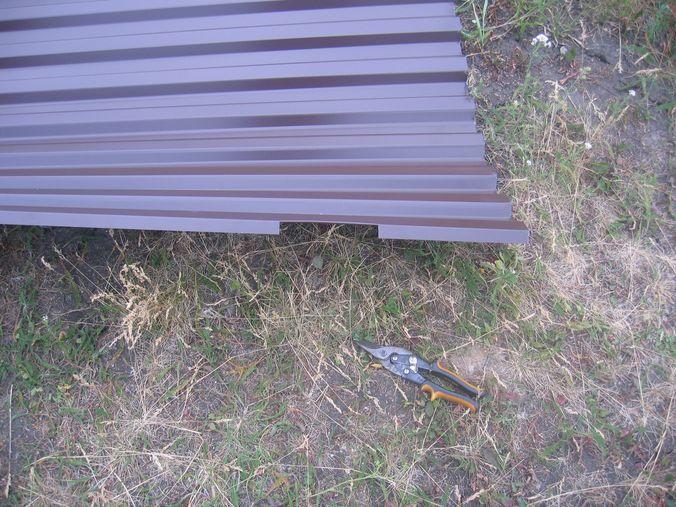 Крепим профнастил на ворота. Под петли делаем вырезы