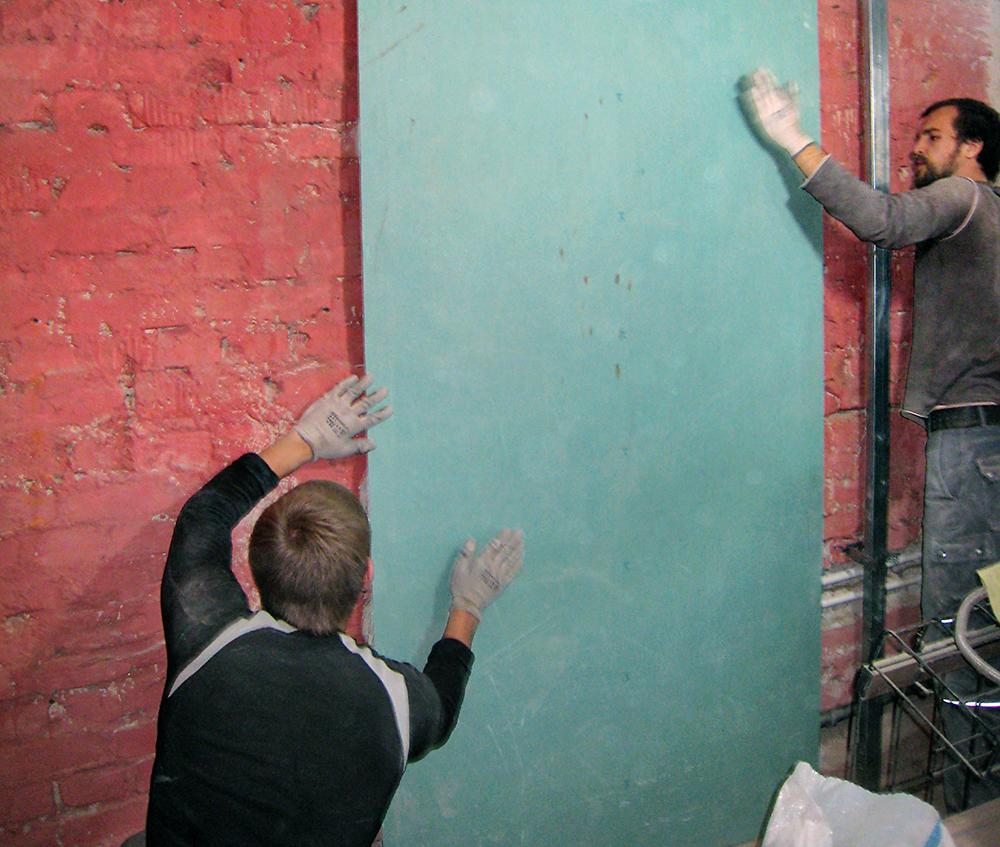 Мастера крепят гипсокартон к кирпичной стене
