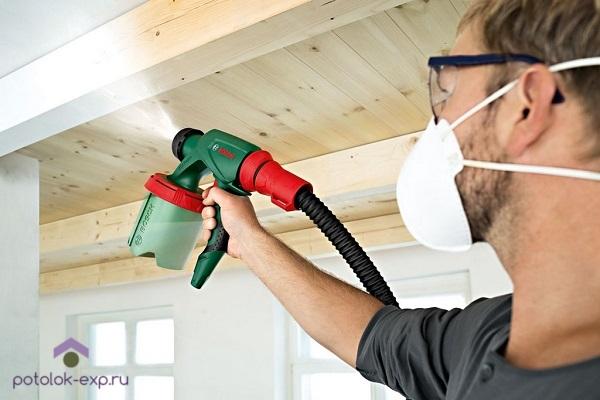 Покраска деревянного потолка с помощью распылителя