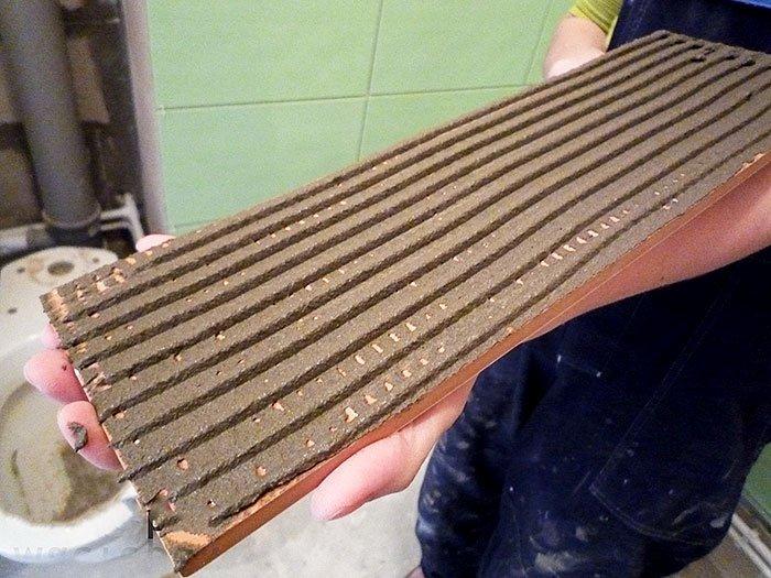 Плитку с равномерным слоем клея прижимаем к сухой прогрунтованной стене.