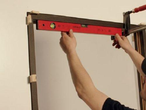 По всему периметру между коробкой и стеной устанавливаются деревянные клинья (минимум 15 шт.). Это повысит прочность крепления коробки. При этом нужно периодически проверять оси