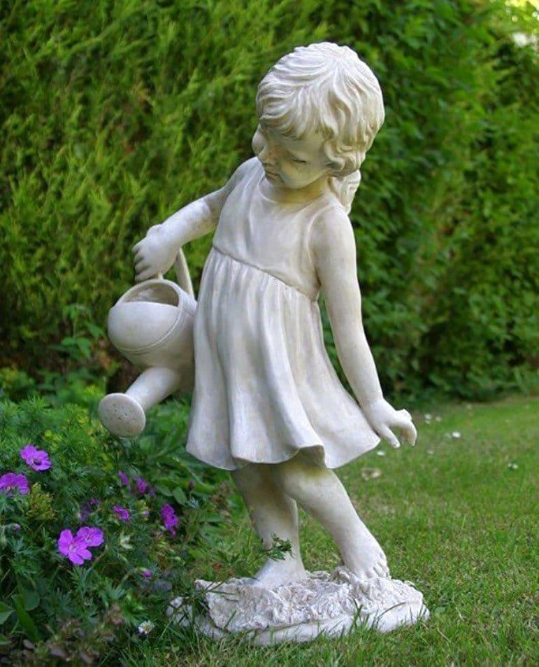 Красивая гипсовая статуэтка девушки, аккуратно поливающая цветы
