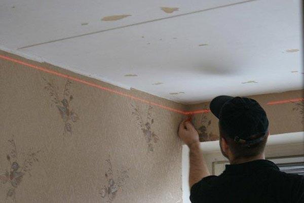 Пользуясь строительным уровнем, производится разметка под установку каркаса на потолок