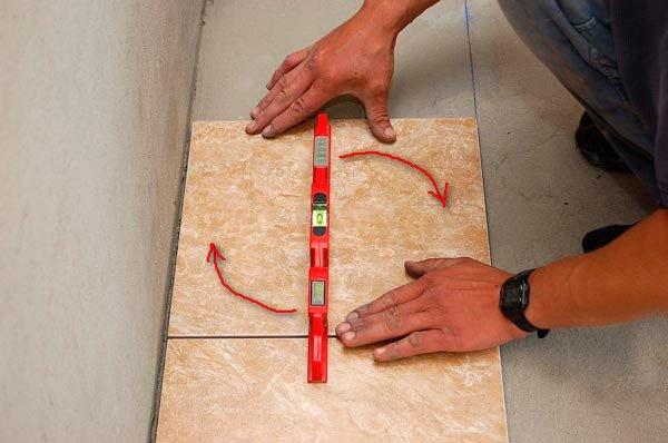Плитка приклеивается плотным нажимом к поверхности: благодаря тонкому слою и одинаковому количеству раствора кафель будет ложиться почти ровно. Для корректировки во время прижима двигайте плитку туда-сюда круговыми движениями.