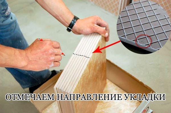 С обратной стороны смотрим направление укладки плитки по стрелке. Отмечаем направление карандашом на торце, чтобы видеть его после нанесения клея.